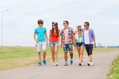 Grupo de adolescentes sonrientes que caminan al aire libre Fotografía de archivo
