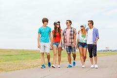 Grupo de adolescentes sonrientes que caminan al aire libre Imagen de archivo