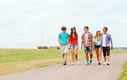 Grupo de adolescentes sonrientes que caminan al aire libre Imágenes de archivo libres de regalías