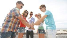 Grupo de adolescentes sonrientes que cuelgan hacia fuera al aire libre almacen de video