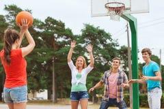 Grupo de adolescentes sonrientes que juegan a baloncesto Foto de archivo
