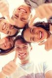 Grupo de adolescentes sonrientes que miran abajo Imagen de archivo libre de regalías