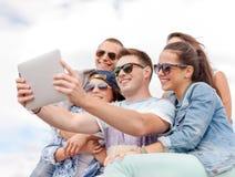 Grupo de adolescentes sonrientes que miran la PC de la tableta Fotografía de archivo libre de regalías
