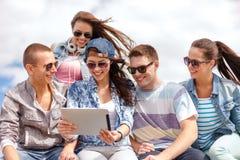 Grupo de adolescentes sonrientes que miran la PC de la tableta Imagenes de archivo