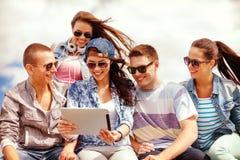 Grupo de adolescentes sonrientes que miran la PC de la tableta Fotografía de archivo