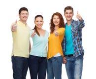 Grupo de adolescentes sonrientes que muestran los pulgares para arriba Imágenes de archivo libres de regalías
