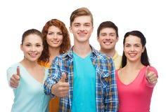 Grupo de adolescentes sonrientes que muestran los pulgares para arriba Imagen de archivo libre de regalías
