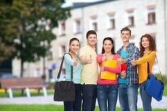Grupo de adolescentes sonrientes que muestran los pulgares para arriba Imagenes de archivo