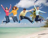 Grupo de adolescentes sonrientes que saltan en aire Foto de archivo