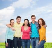 Grupo de adolescentes sonrientes sobre el cielo azul y la hierba Imágenes de archivo libres de regalías