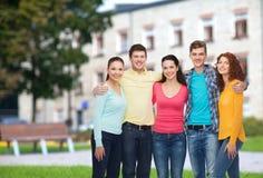 Grupo de adolescentes sonrientes sobre fondo del campus Fotos de archivo libres de regalías
