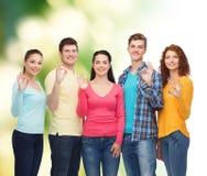 Grupo de adolescentes sonrientes sobre fondo verde Fotos de archivo
