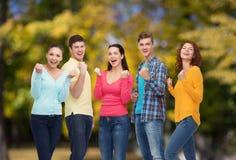 Grupo de adolescentes sonrientes sobre parque verde Fotos de archivo libres de regalías