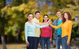 Grupo de adolescentes sonrientes sobre parque verde Foto de archivo libre de regalías
