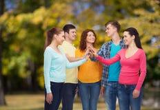 Grupo de adolescentes sonrientes sobre parque verde Imagenes de archivo