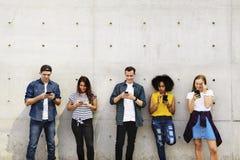 Grupo de adultos jovenes al aire libre usando smartphones junto y el ch Fotografía de archivo