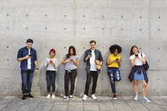 Grupo de adultos jovenes al aire libre usando smartphones junto y el ch Foto de archivo