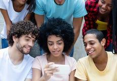 Grupo de adultos jovenes internacionales que miran el teléfono fotografía de archivo libre de regalías