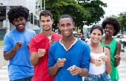 Grupo de adultos jovenes internacionales que señalan en la cámara Foto de archivo