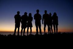 Grupo de adultos jovenes que admiran puesta del sol por la playa Imagen de archivo