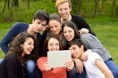 Grupo de adultos jovenes que hojean una tableta imagen de archivo
