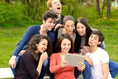 Grupo de adultos jovenes que hojean una tableta afuera Foto de archivo