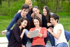 Grupo de adultos jovenes que hojean una tableta afuera fotografía de archivo