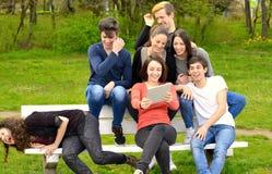 Grupo de adultos jovenes que hojean una tableta afuera imagenes de archivo