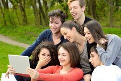 Grupo de adultos jovenes que hojean una tableta afuera Foto de archivo libre de regalías