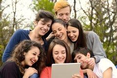 Grupo de adultos jovenes que hojean una tableta afuera imagen de archivo