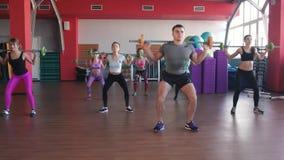 Grupo de adultos masculinos y femeninos fuertes que sostienen barbells en estudio del ejercicio del ftness metrajes