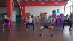 Grupo de adultos masculinos y femeninos fuertes que sostienen barbells en estudio del ejercicio del ftness almacen de video