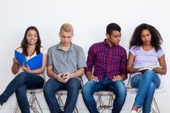 Grupo de adultos novos internacionais desempregados em uma sala de espera FO imagens de stock