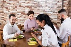 Grupo de adultos que cenan con smartphones Imagen de archivo libre de regalías