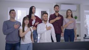Grupo de aficionados deportivos de los amigos que canta himno nacional antes de mirar campeonato de los deportes en la TV junto e almacen de metraje de vídeo