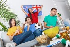Grupo de aficionados deportivos de los amigos que mira el partido en las camisas coloridas referidas imagen de archivo