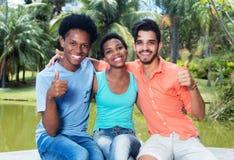 Grupo de afro-americano feliz e homem e mulher do latino que mostram o polegar Fotos de Stock