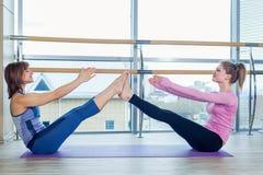 Grupo de ajuda das mulheres do instrutor pessoal de Pilates da ginástica aeróbica em uma classe do gym Fotografia de Stock