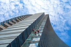 Grupo de alpinistas en el servicio para la limpieza de ventanas del rascacielos imagen de archivo libre de regalías