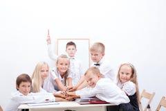 Grupo de alumnos adolescentes Ellos que llevan a cabo sus manos Foto de archivo libre de regalías