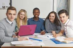 Grupo de alumnos adolescentes que trabajan junto en sala de clase Foto de archivo