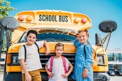 grupo de alumnos adorables que se inclinan detrás en el autobús escolar y la mirada fotografía de archivo libre de regalías