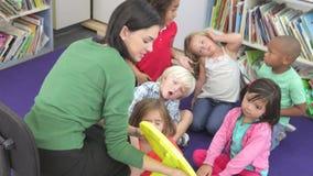 Grupo de alumnos elementales de la edad que aprenden decir tiempo almacen de metraje de vídeo