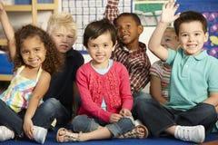 Grupo de alumnos elementales de la edad que contestan a la pregunta en el Cla Imagen de archivo libre de regalías