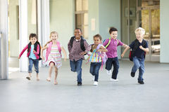 Grupo de alumnos elementales de la edad que corren afuera Foto de archivo libre de regalías