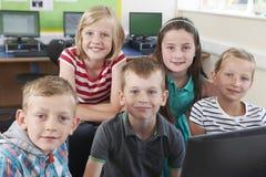 Grupo de alumnos elementales en clase del ordenador fotos de archivo