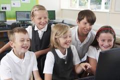Grupo de alumnos elementales en clase del ordenador fotos de archivo libres de regalías