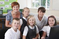 Grupo de alumnos elementales en clase del ordenador con el profesor foto de archivo libre de regalías