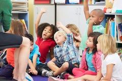 Grupo de alumnos elementales en la pregunta de contestación de la sala de clase imagenes de archivo