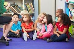 Grupo de alumnos elementales en la sala de clase que trabaja con el profesor Fotos de archivo libres de regalías